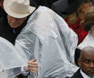 Former President George W. Bush keeps covered under the rain during the inauguration ceremonies in Washington